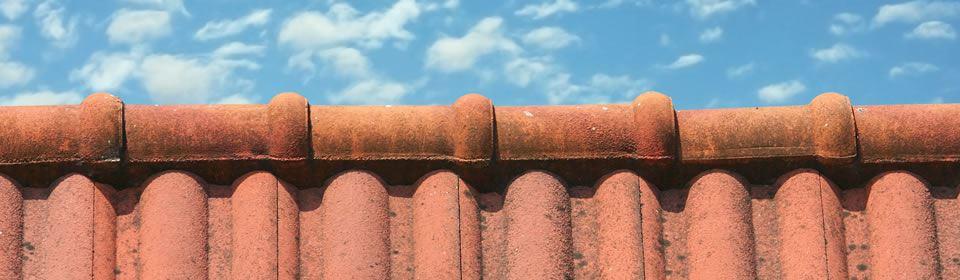 bovenkant rood pannendak met nokvorst en blauwe, lichtbewolkte lucht